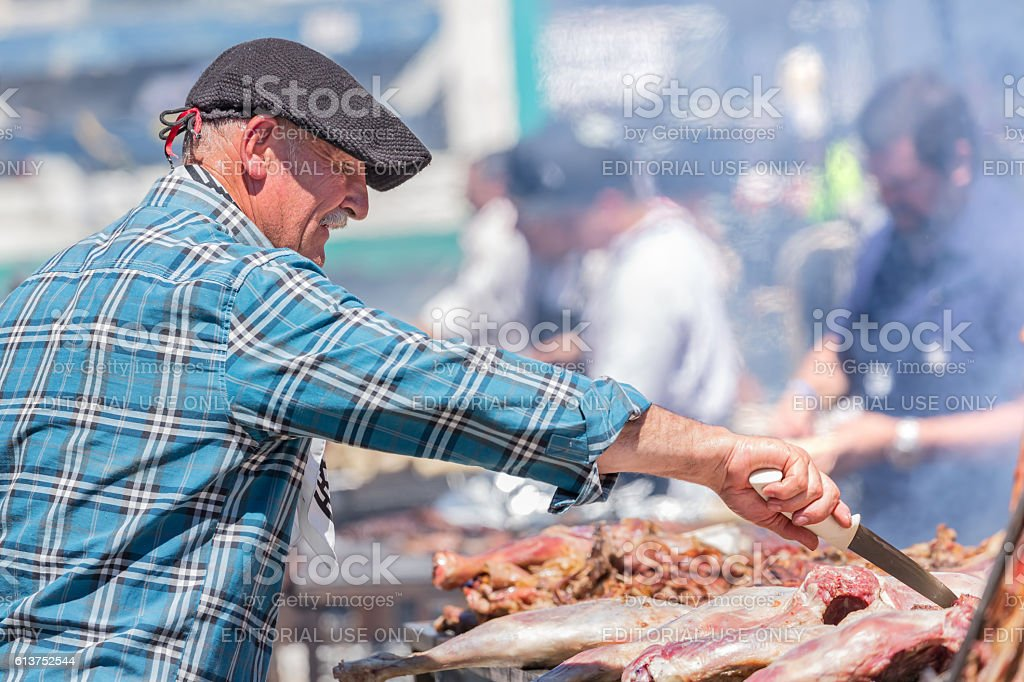 Argentinean asado (BBQ) with old gaucho controlling meet stock photo