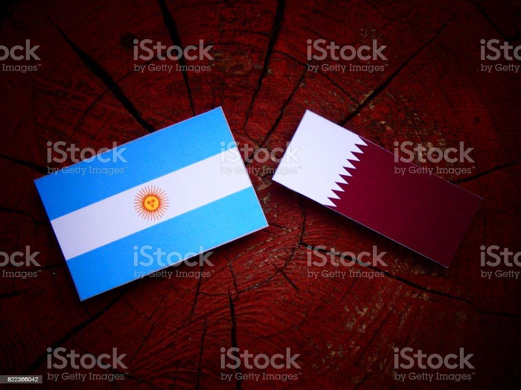 Argentinian flag with Qatari flag on a tree stump isolated stock photo