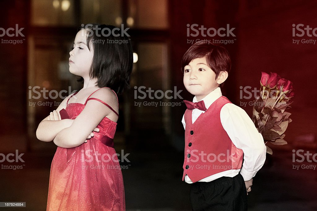 Argument Between Little Girl and Boy Holding Bouquet of Roses royalty-free stock photo
