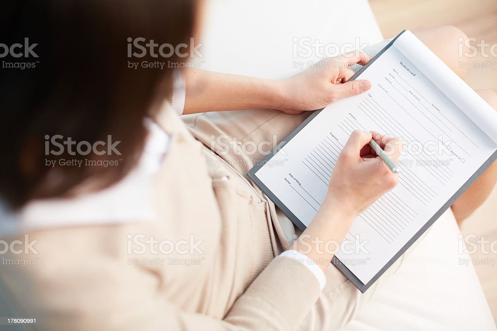 Arial view of woman filling out medical questioner stock photo