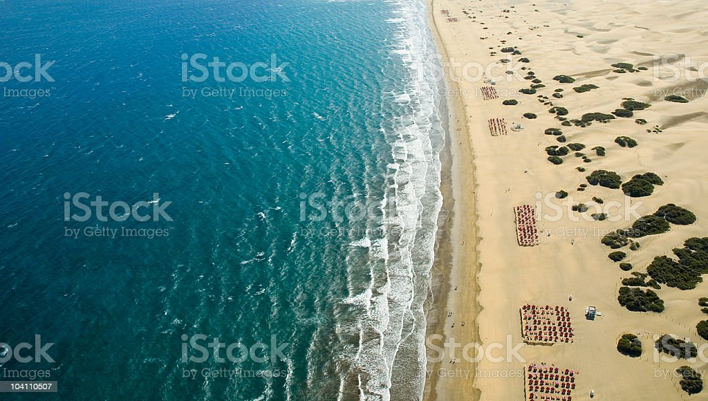 Ariel view of ocean against the beach with rows of chairs stock photo