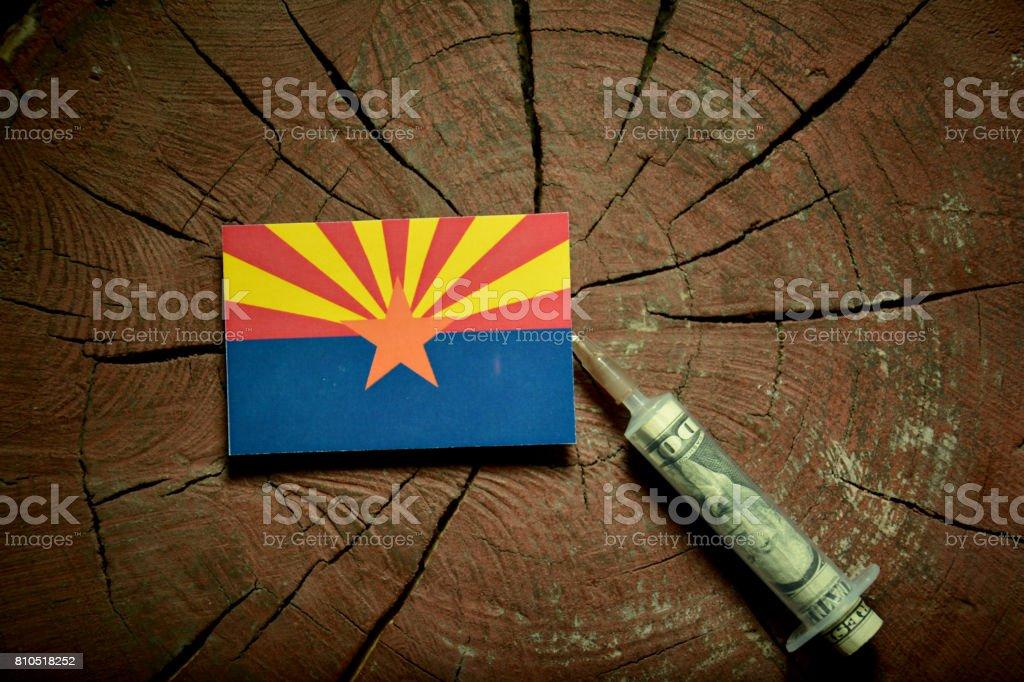 Arizona flag on a stump with syringe injecting money in flag stock photo