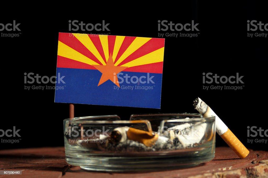 Arizona flag with burning cigarette in ashtray isolated on black background stock photo