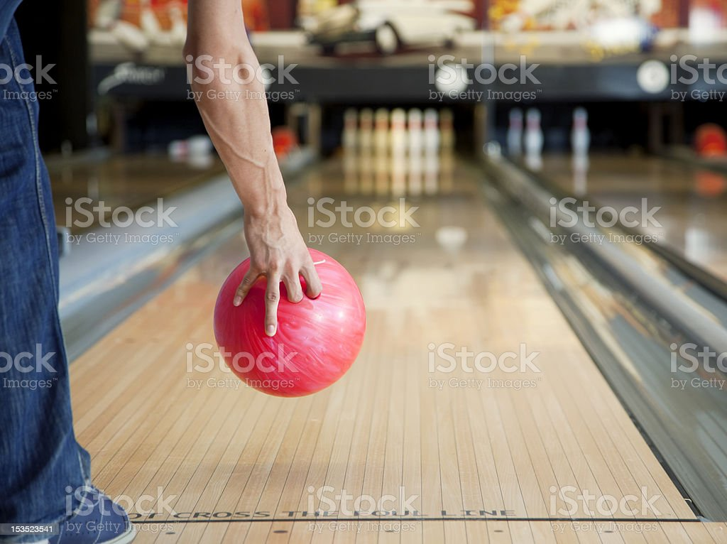 Arm holding red bowling ball above skittles alley stock photo
