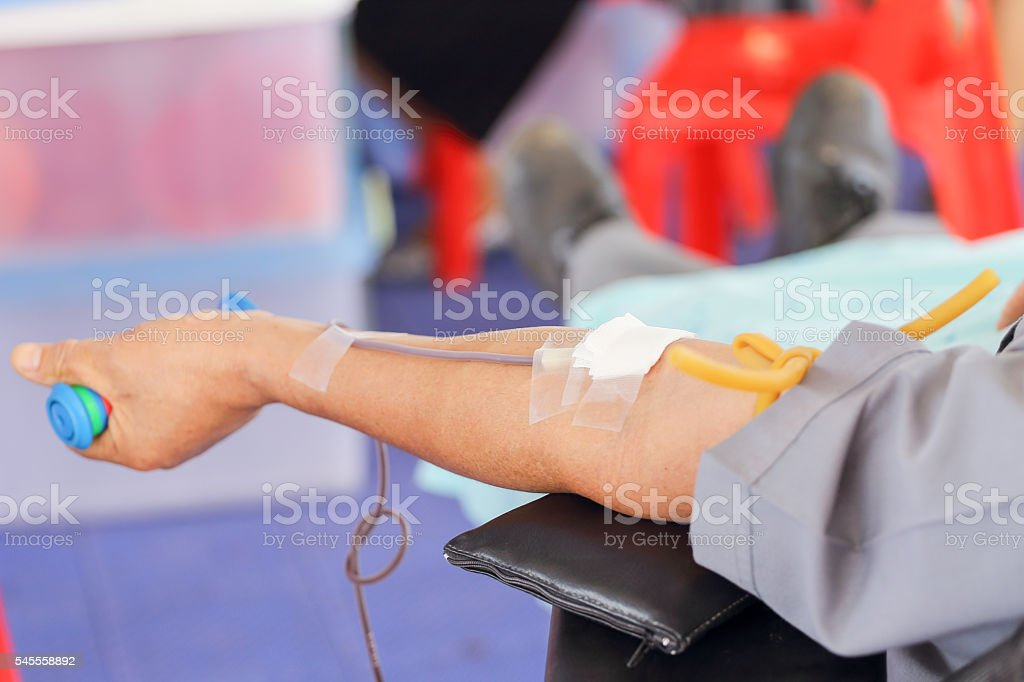 arm of a donor donating blood at hemotransfusion station stock photo