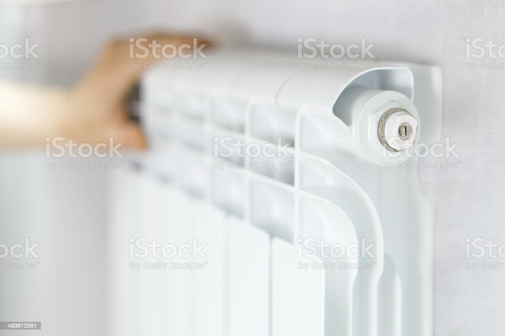 Arm put on  heating white radiator. stock photo