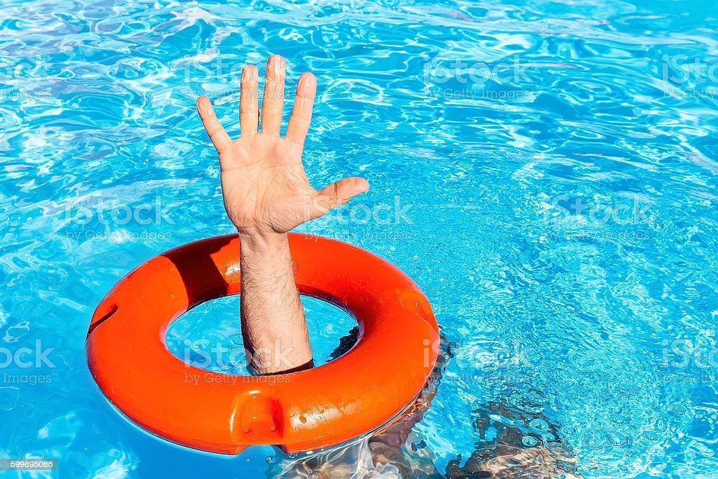 Arm through orange buoy in swimming pool stock photo