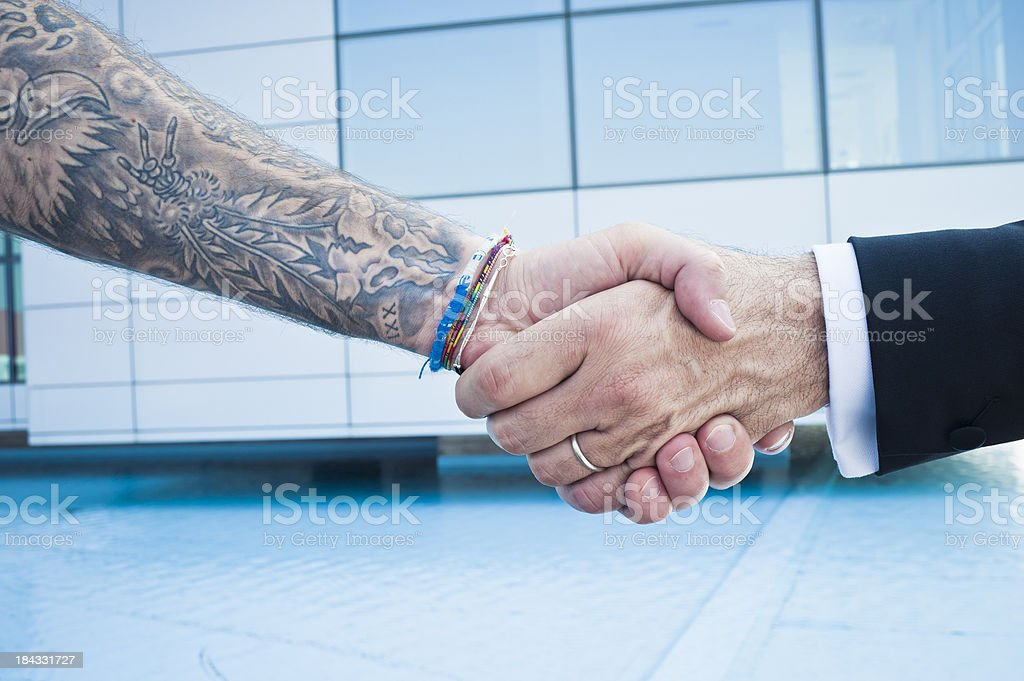 Arm with tattoos and arm in suit shaking hands royalty-free stock photo