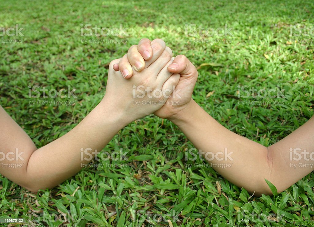 Arm wrestle on the grass stock photo