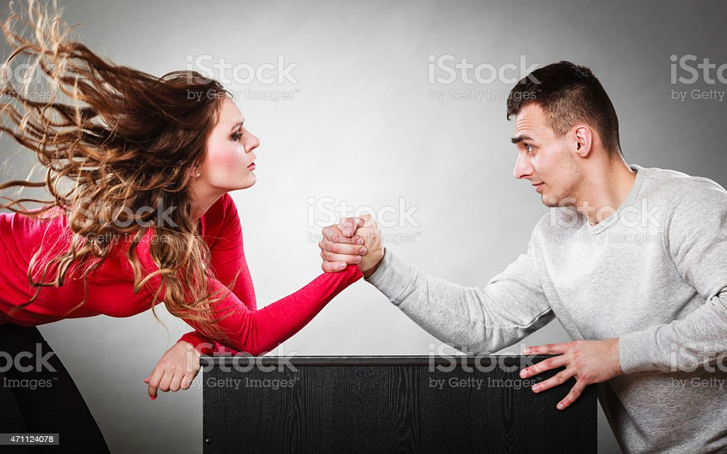 Arm wrestling challenge between young couple stock photo