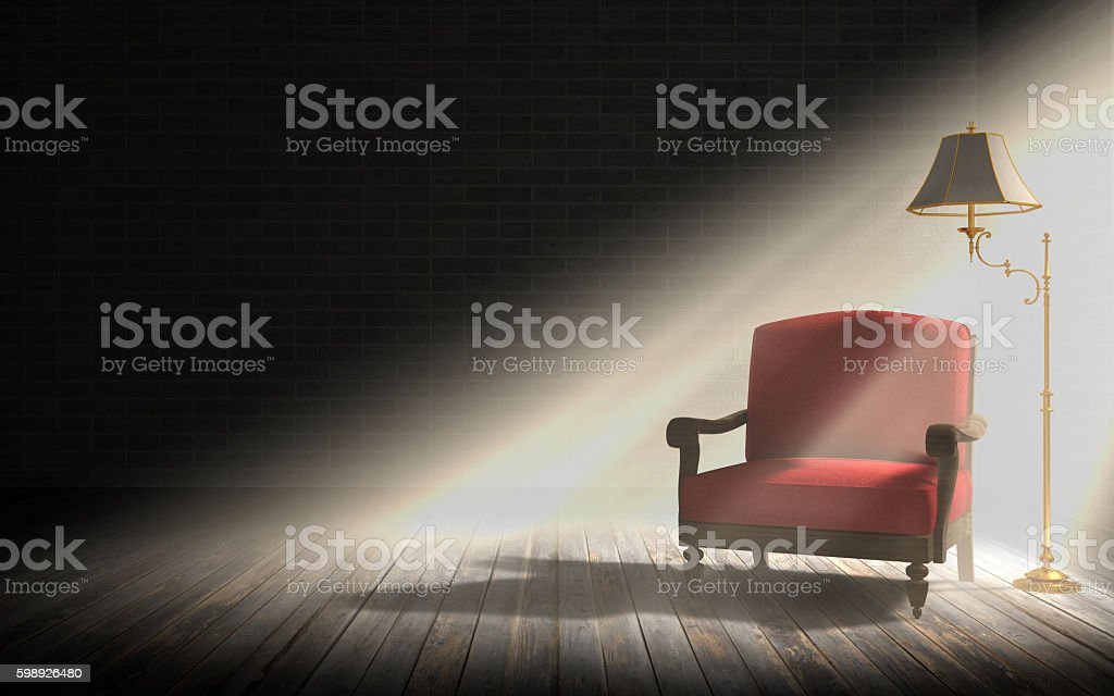 Armchair and floor lamp in dark room with sun rays stock photo