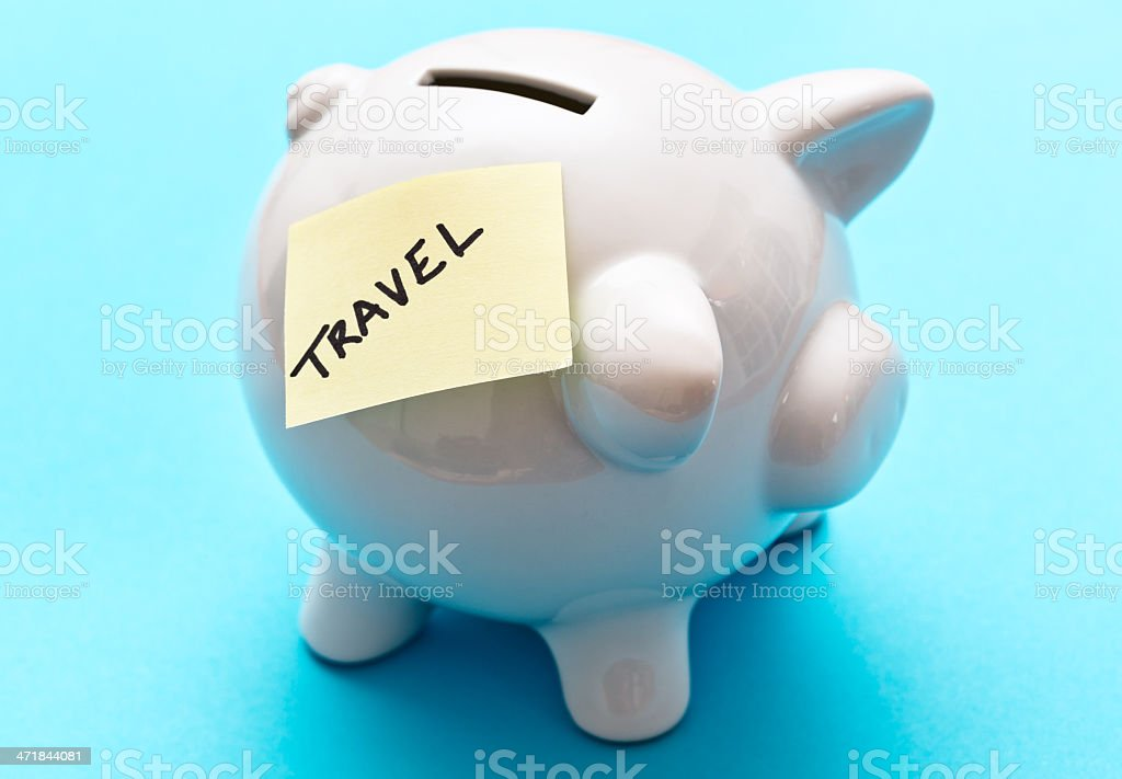 Armchair traveler targets his saving in piggybank labeled TRAVEL royalty-free stock photo