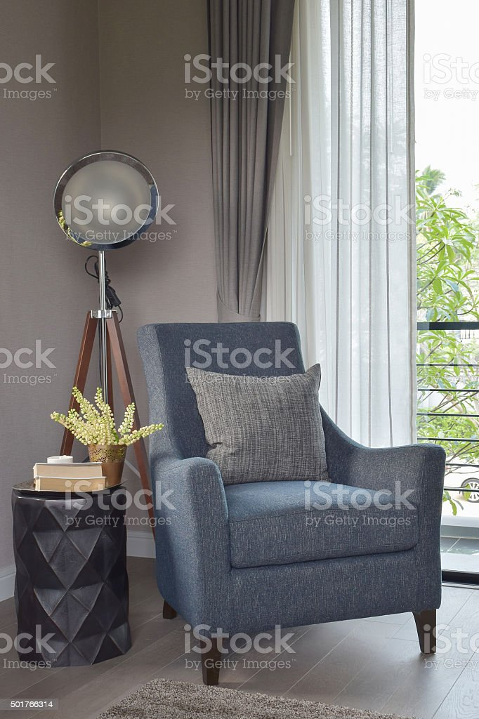 armchair with gray pillow and retro lamp in living room stock photo