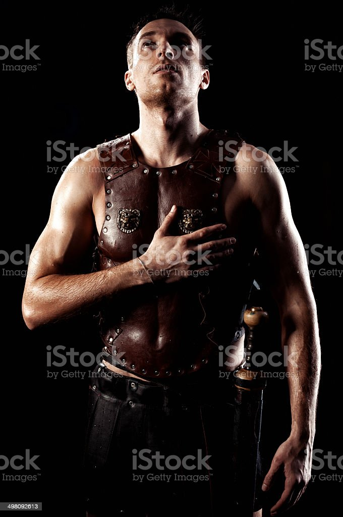 Armed ancient soldier swearing on isolated black background. stock photo