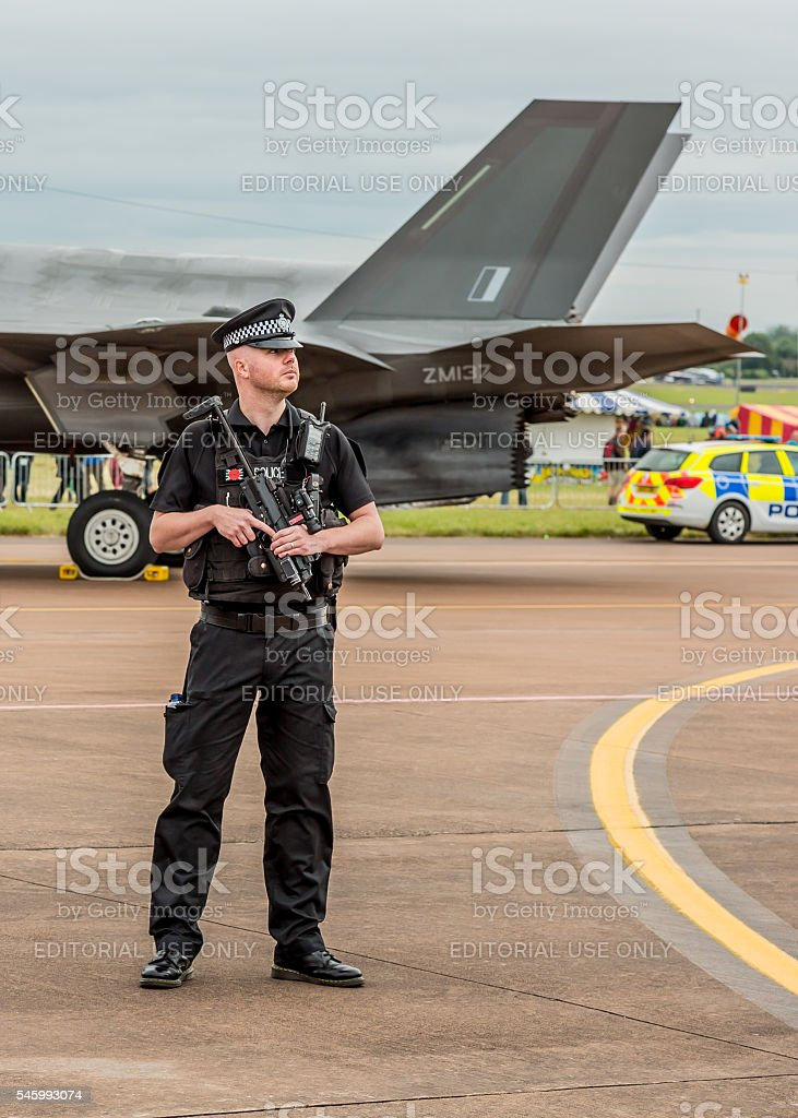 Armed British police officer & fighter jet stock photo