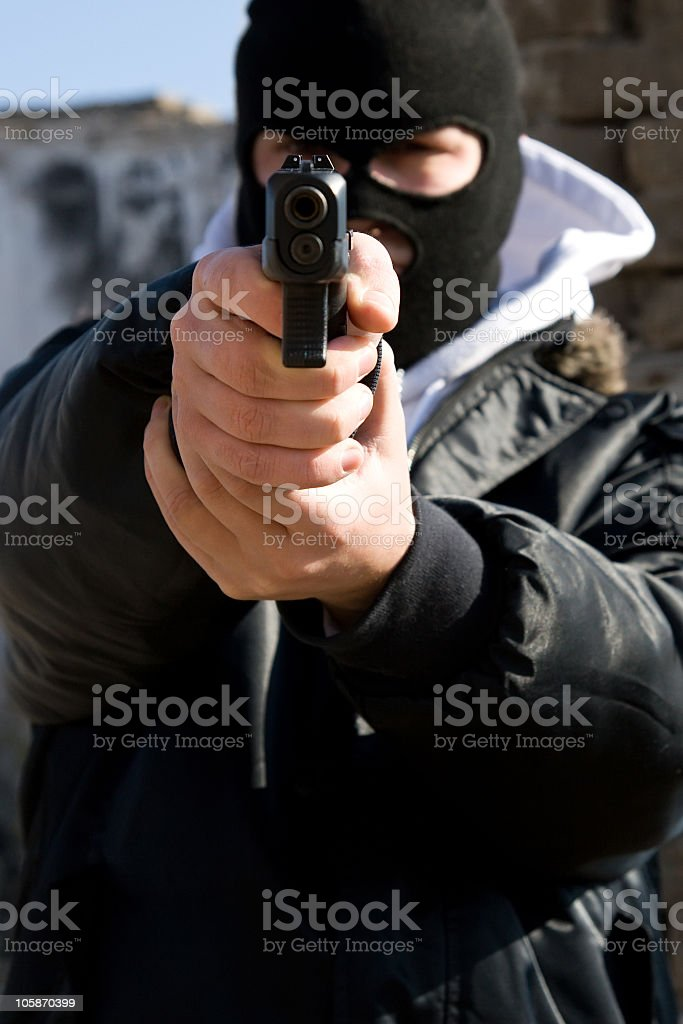 Armed criminal aiming you stock photo
