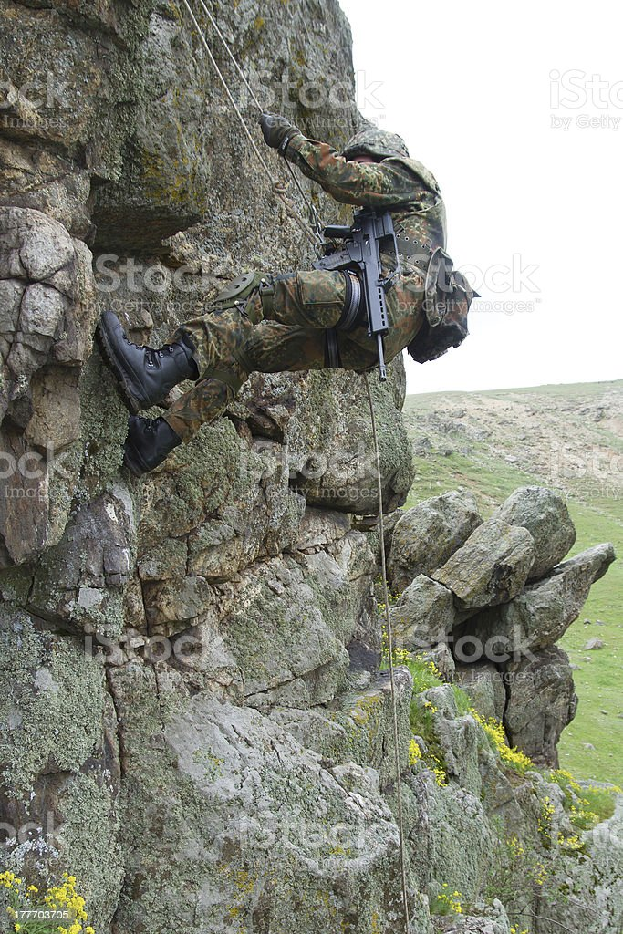 Armed military alpinist climbing royalty-free stock photo