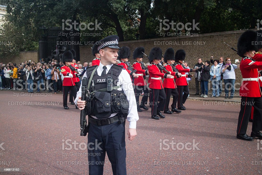 Armed police officer keeping watch as the Queens Guard pass stock photo