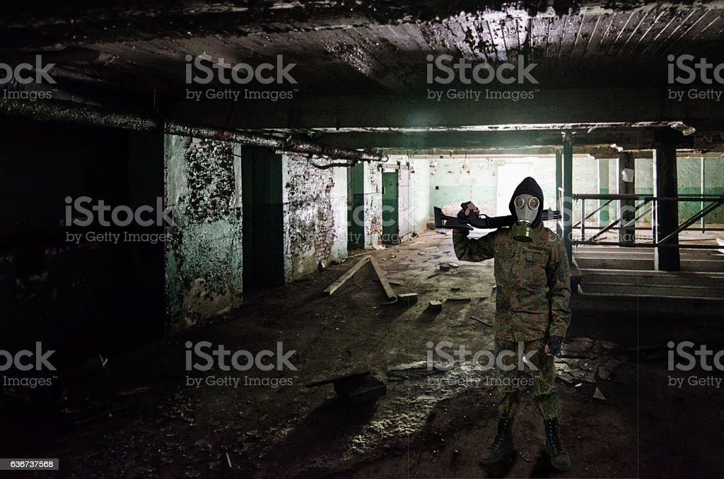 Armed soldier with gas mask standing in abandoned basement stock photo
