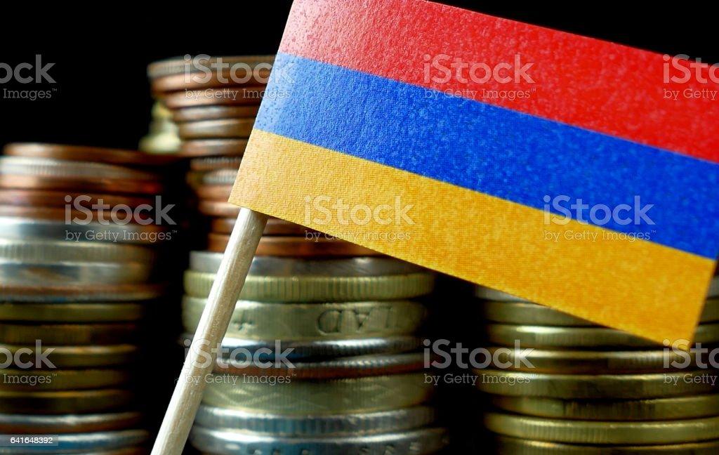Armenia flag waving with stack of money coins macro stock photo