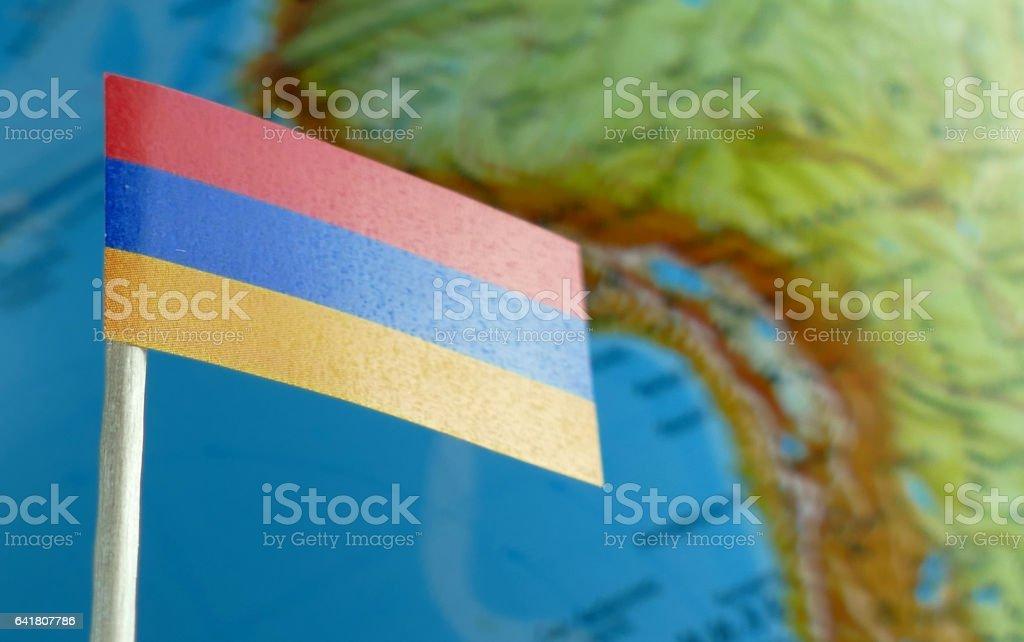 Armenia flag with a globe map as a background macro stock photo