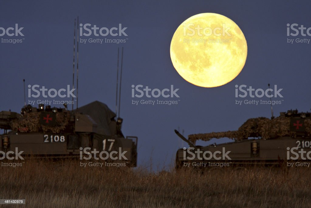 Armored vehicles under a full moon stock photo