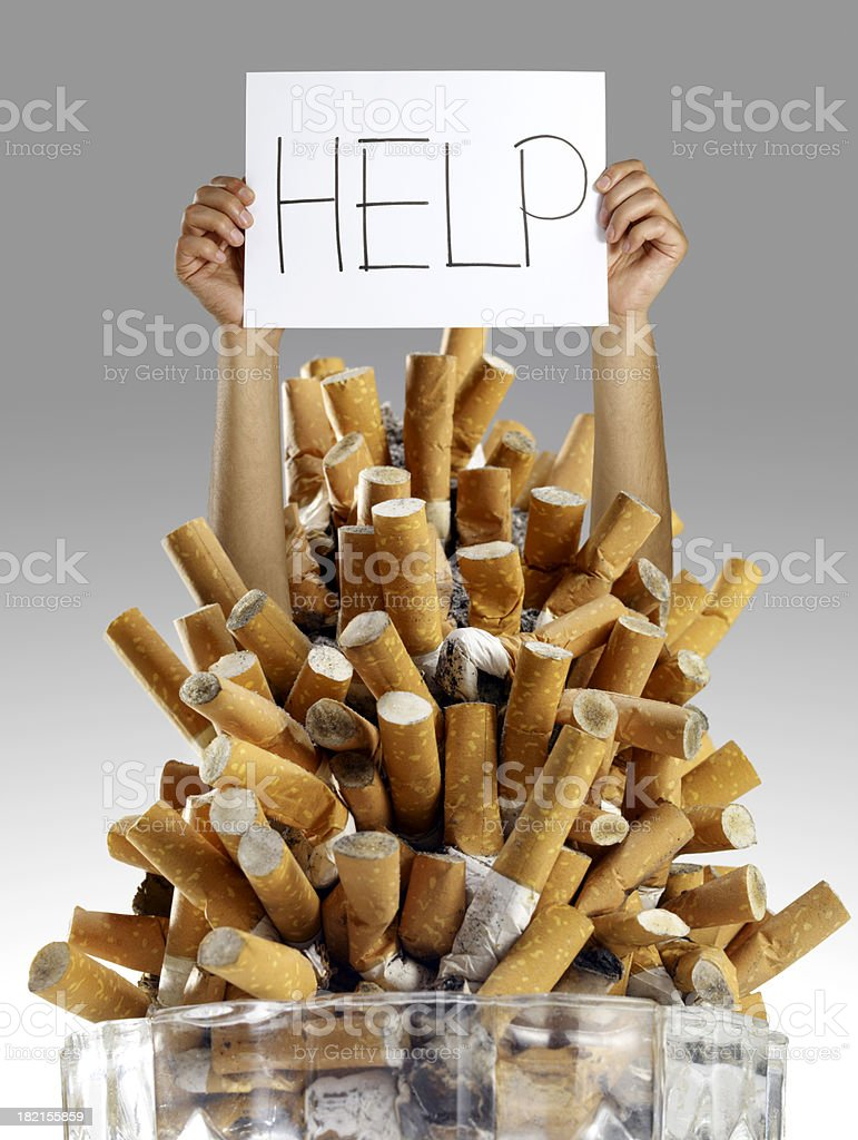 Arms holding a help sign above a glass of used cigarettes royalty-free stock photo