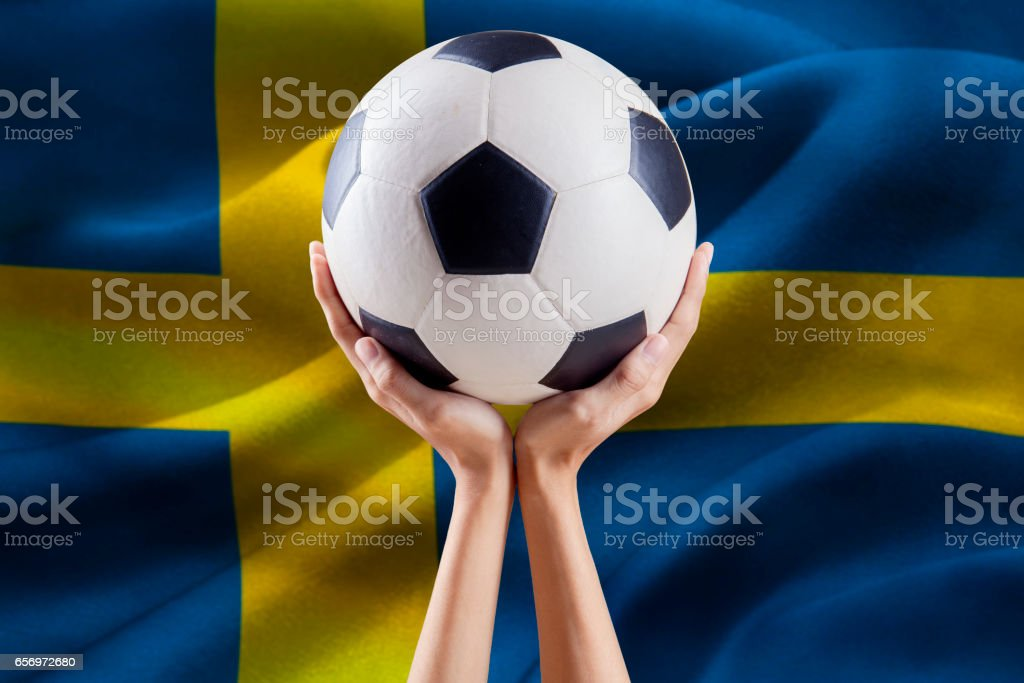 Arms holding ball with flag of Sweden stock photo
