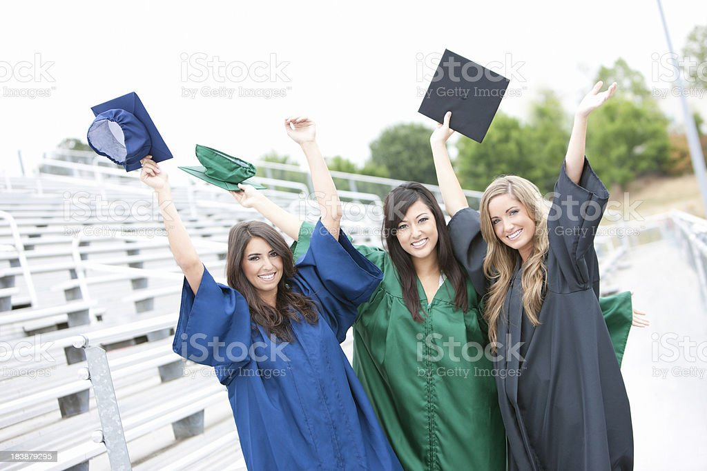Arms in Air, Cheerful Young Women Graduates Wearing Cap, Gown royalty-free stock photo