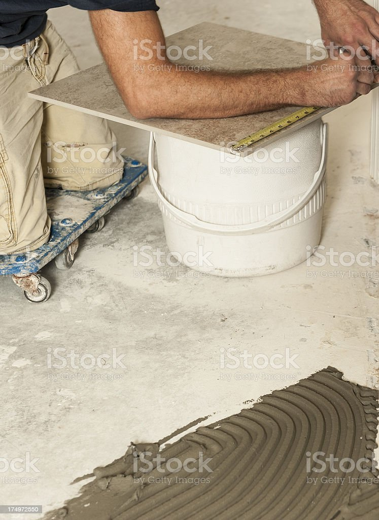Arms measuring tiles on white bucket to install on floor. royalty-free stock photo