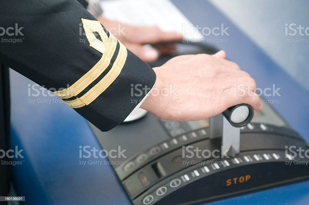 Arms of a man in uniform controlling navigation lever royalty-free stock photo
