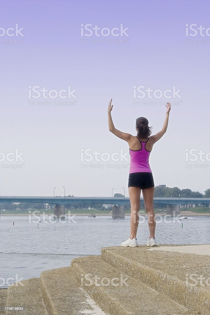 Arms raised at riverside stock photo
