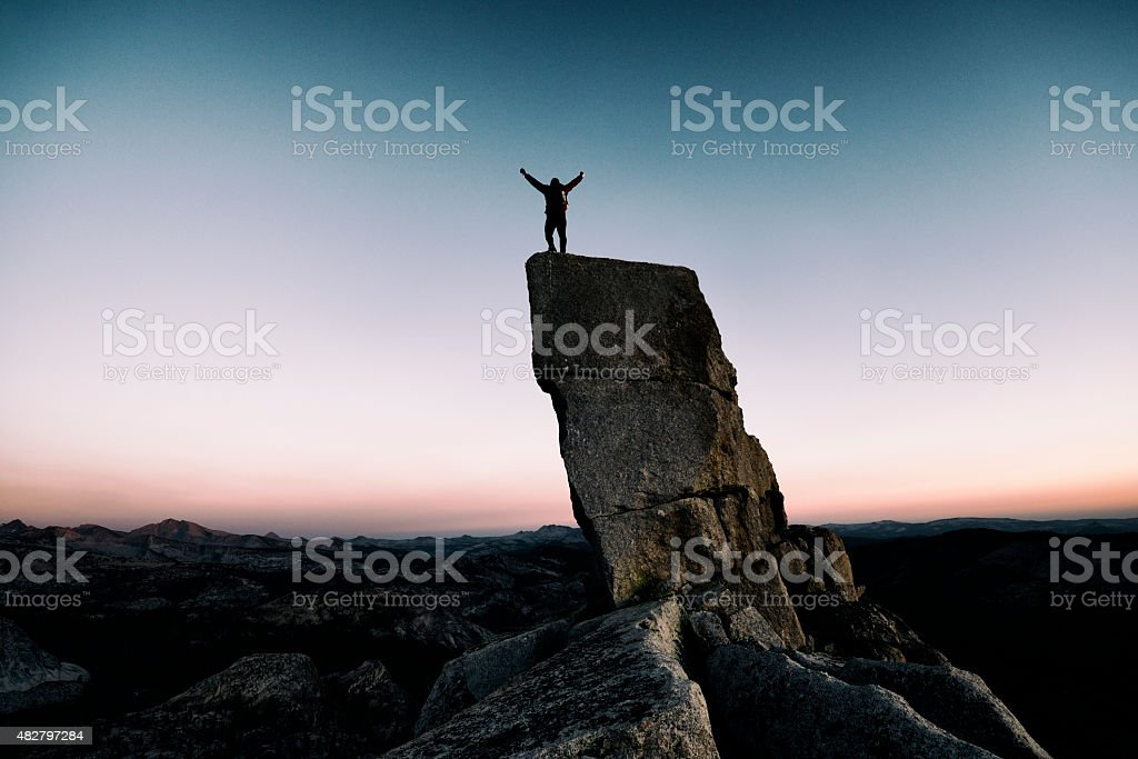 arms raised on a pinnacle stock photo