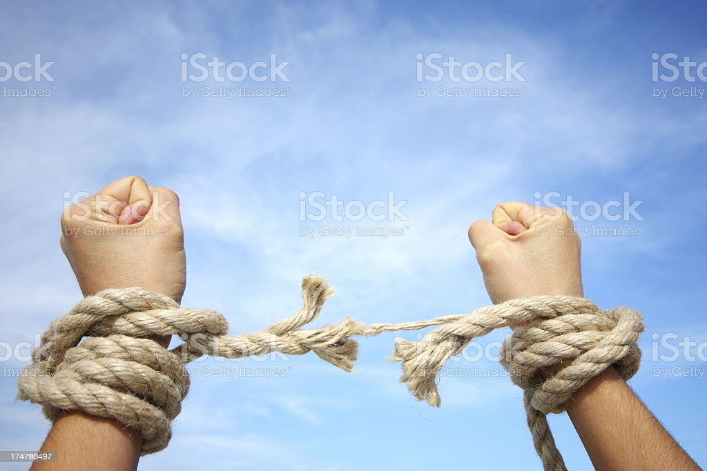 Arms tied in rope break free beneath a cloudy sky stock photo