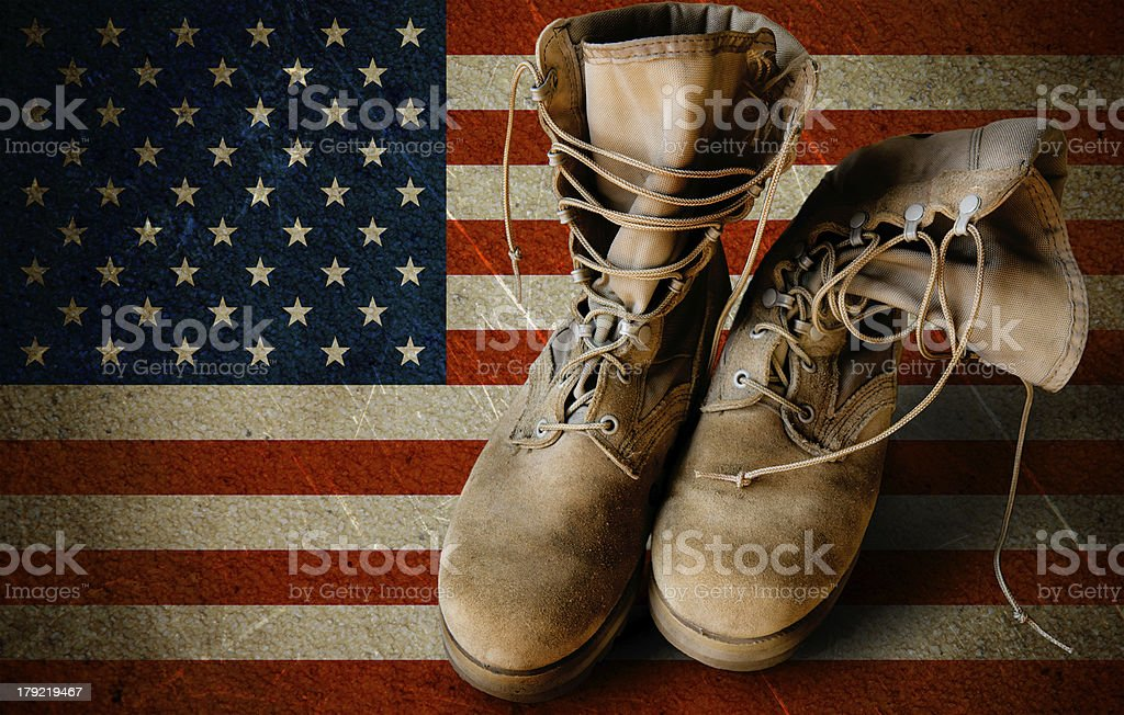 Army boots on sandy flag background stock photo
