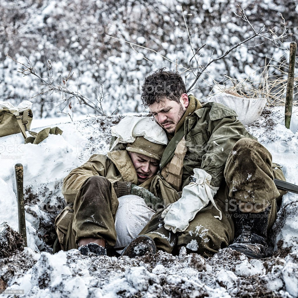 WWII US Army Combat Soldier Comforting Terrified Crying Foxhole Buddy stock photo