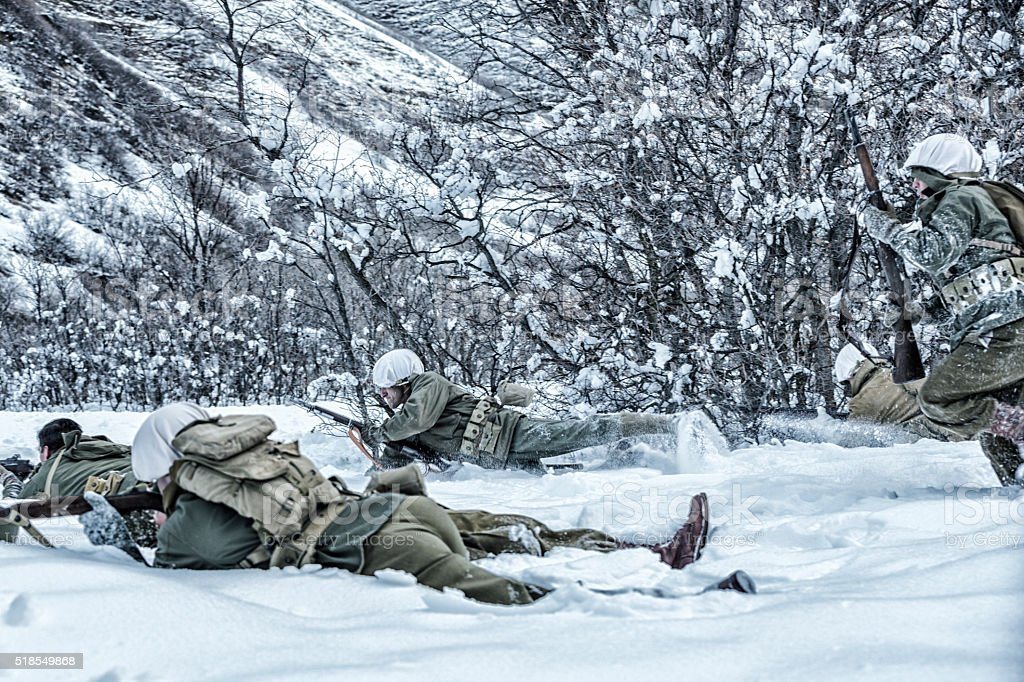 WWII US Army Combat Soldiers Scrambling To Return Enemy Fire stock photo