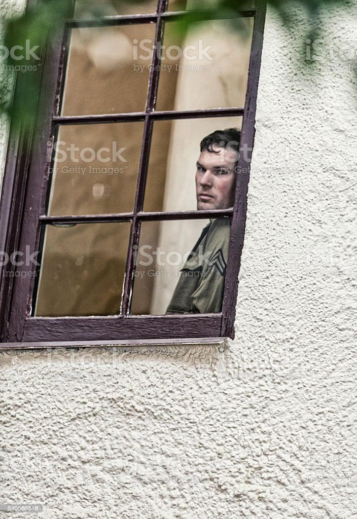 WWII US Army Corporal Military Soldier Looking Through Window stock photo