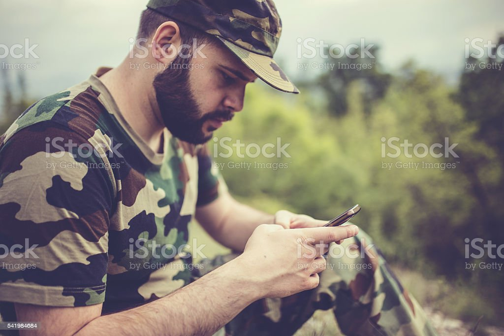 Army guy with smart phone stock photo