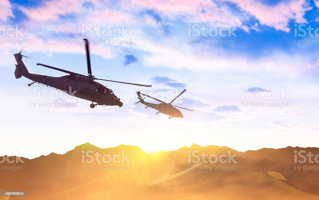Army helicopters flying over desert stock photo