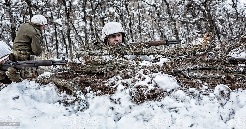 WWII US Army Infantry Snipers Shooting Rifles Behind Winter Camouflage stock photo