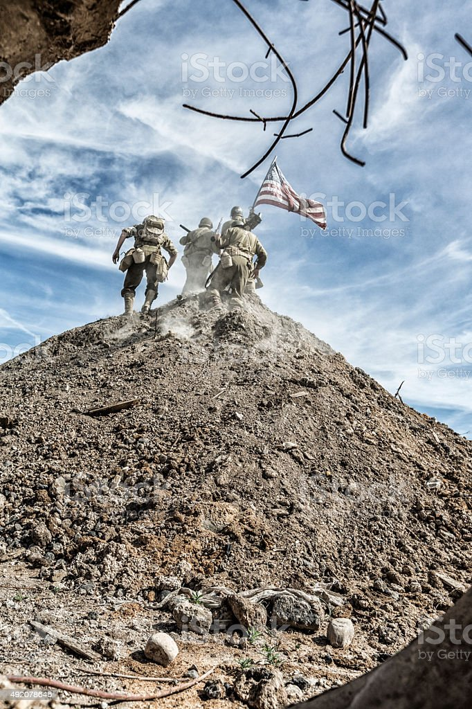 WWII US Army Infantry Squad Claiming Hill With American Flag stock photo