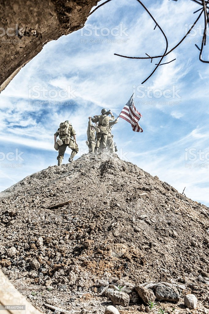 WWII US Army Infantry Squad Climbing Hill With American Flag stock photo