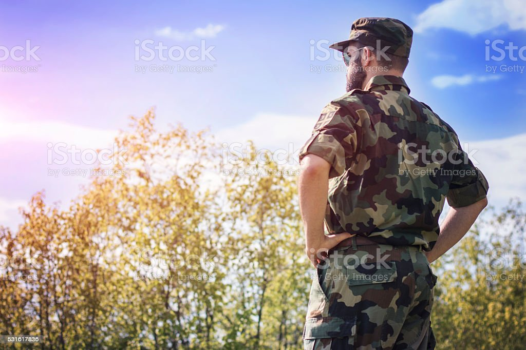Army man scouting from high hills stock photo