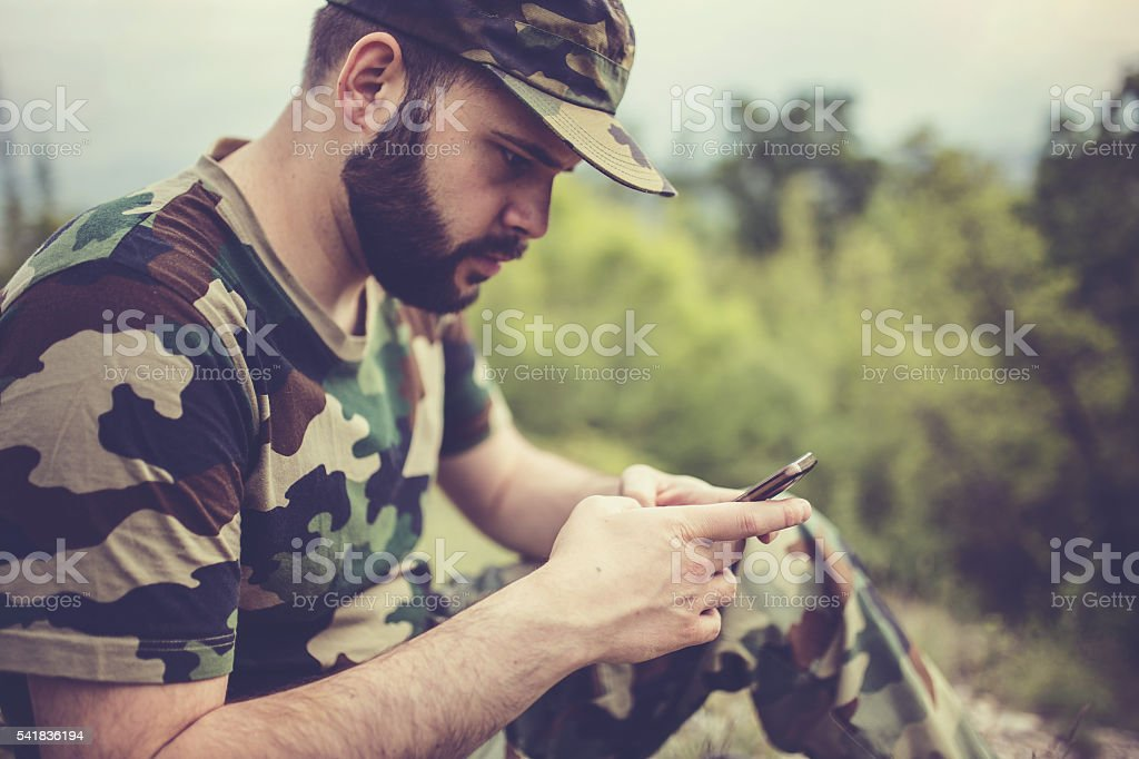 Army man with smart phone stock photo