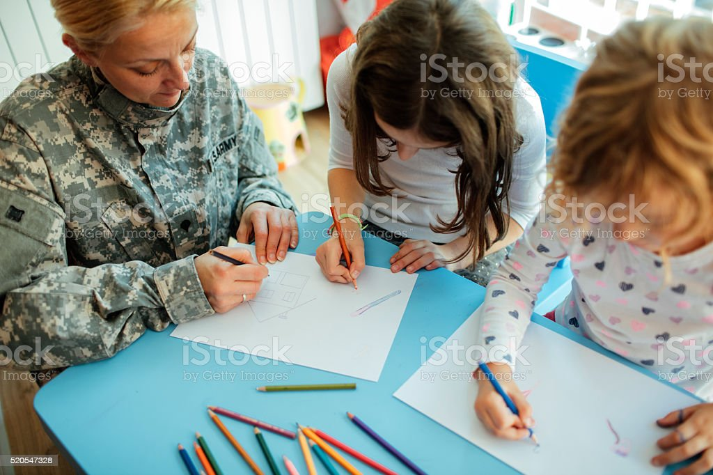 Army Mom Coloring With Her Kids. stock photo