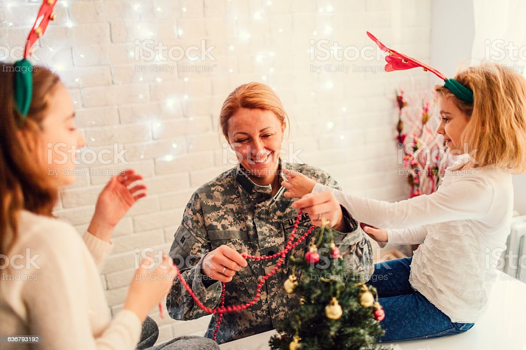 Army Mom Decorating Christmas Tree With Her Kids. stock photo