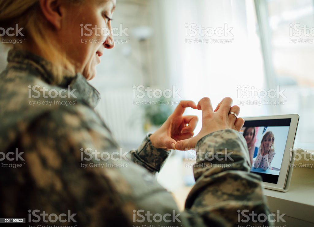 Army Mom Talking With Her Children Over Tablet. stock photo