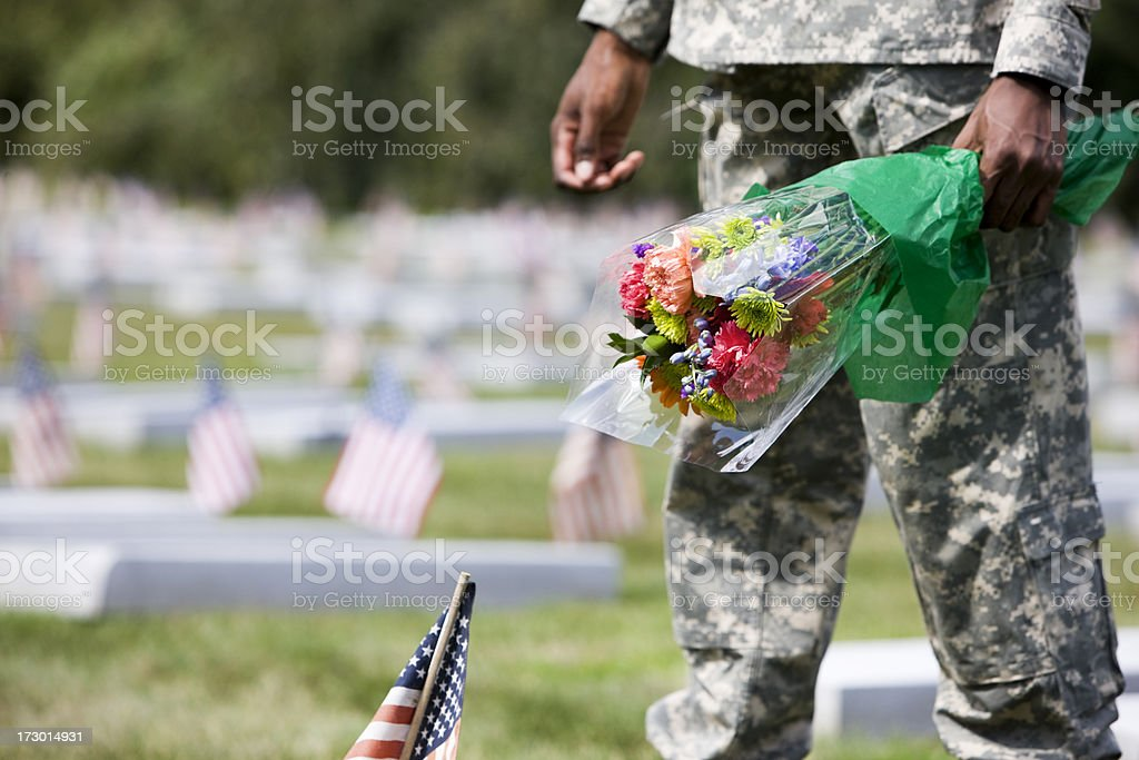 Army Soldier at Military Cemetery with Flower Bouquet, Copy Space stock photo