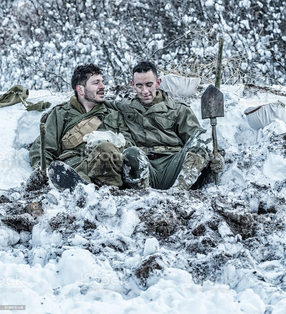 WWII US Army Soldier Buddies Joking In Foxhole stock photo
